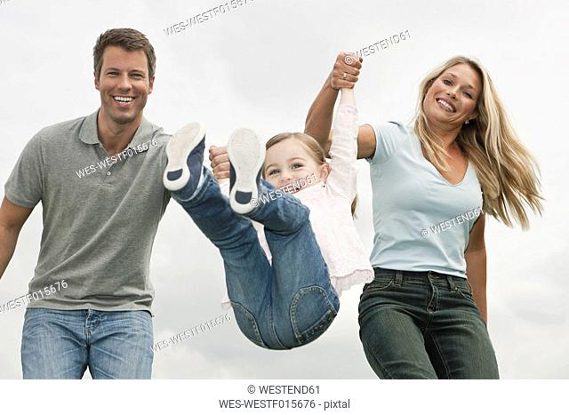 Germany, Cologne, Parents swings her daughter 2-3 Years, smiling