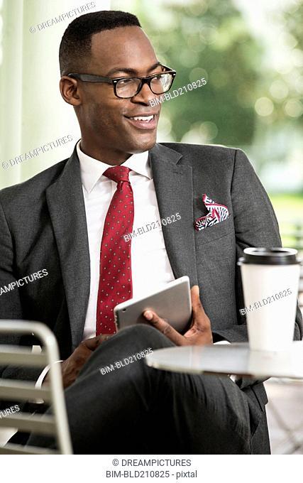 Black businessman using digital tablet at cafe