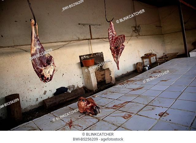 Fresh goat meat is being offered on public market in bad hiegene conditions, dried blood on tiled surface, Rwanda, Nyamirambo, Kigali