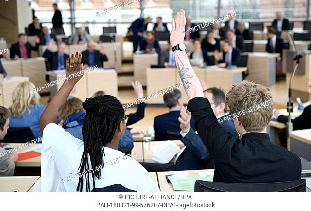 21 March 2018, Germany, Kiel: The members of paarliament of Germany's Alliance 90/The Greens Aminata Tourè (L) and Lasse Petersdotter (R) raise their hands...