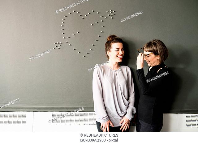 Two women by wall with heart shape
