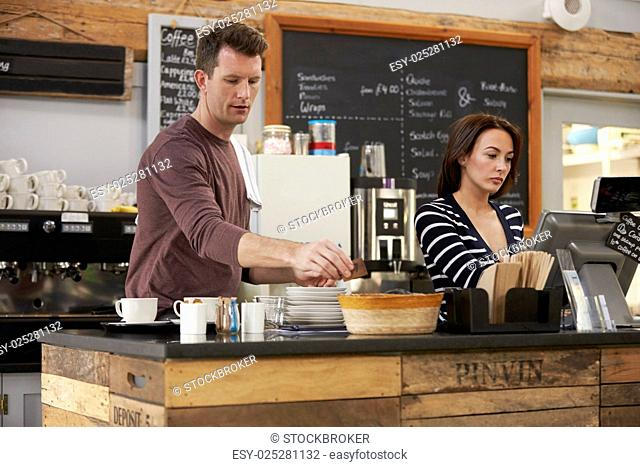 Cafe owners working behind the counter of their coffee shop