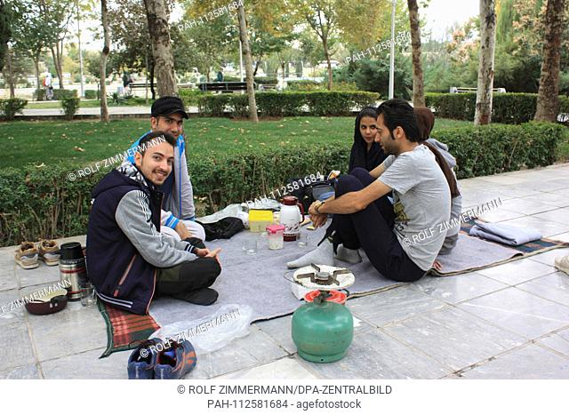 Iran - Teenagers picnicking in a park near the 33-arch bridge on the Zayandeh Rud River in Isfahan (Esfahan), capital of the province of the same name