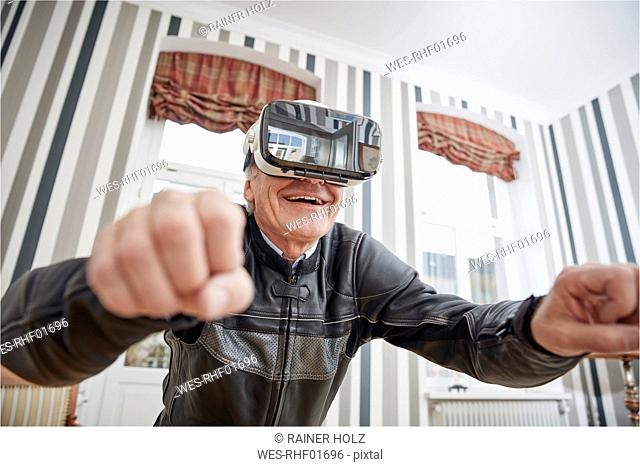 Senior man in motorcycle suit wearing VR glasses