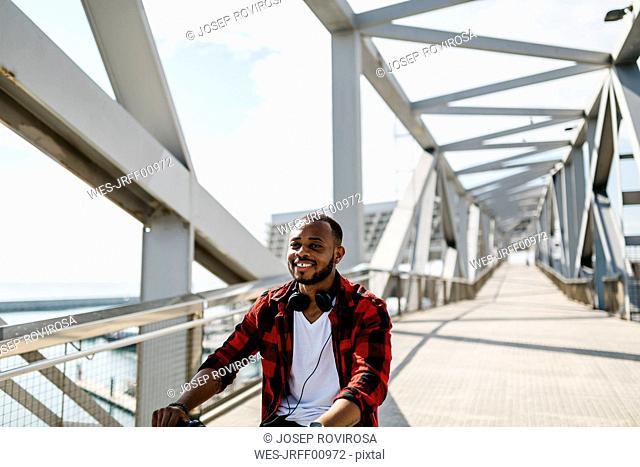 Smiling man riding bicycle on a bridge