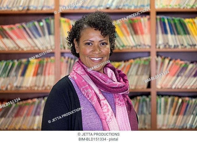 Mixed race receptionist smiling near wall of medical files