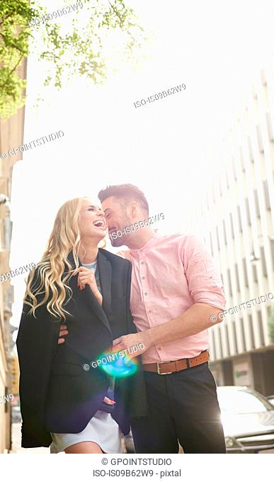 Man in street sharing suit jacket with woman