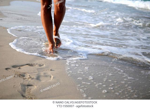 Legs of young woman walking on the beach