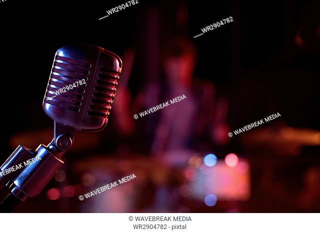 Close-up of retro microphone against band background
