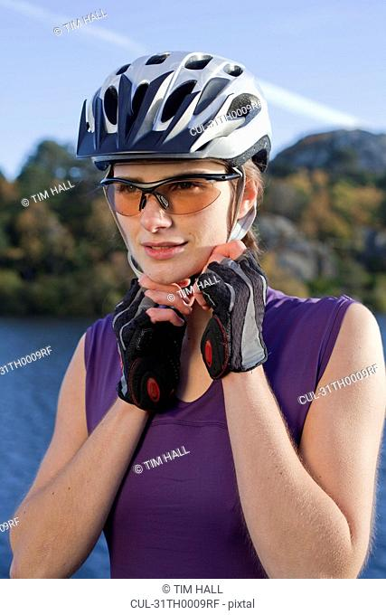 woman putting on a cycling helmut