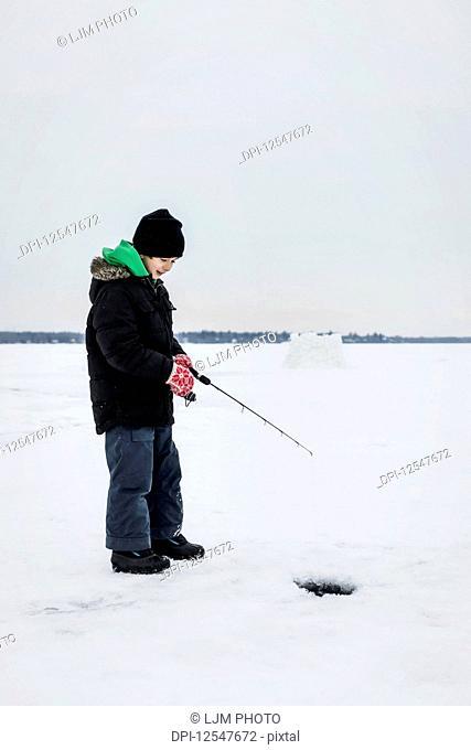 Boy patiently waiting for a bite while ice fishing at Wabamun Lake; Wabamun, Alberta, Canada