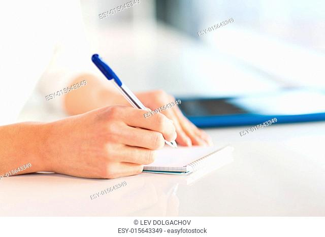 business, education, people and lifestyle concept - close up of woman hands with pen writing to notepad