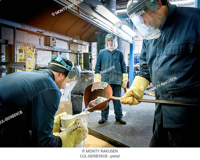 Workers pouring molten aluminium alloy into ceramic mould in precision casting factory