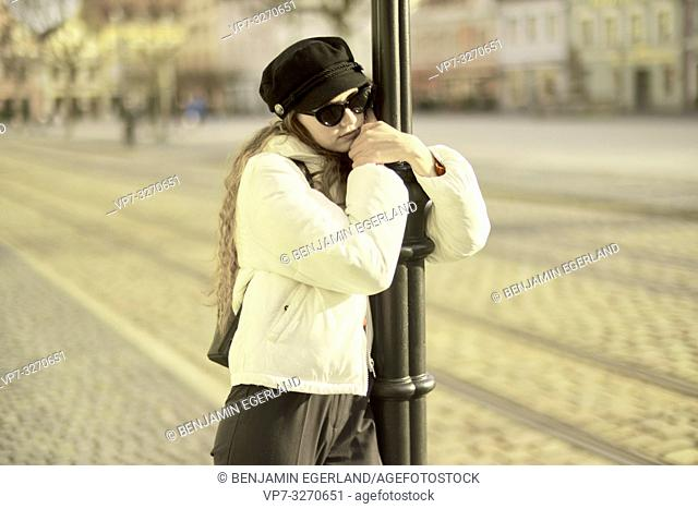 young woman embracing street lamp post, in city Cottbus, Brandenburg, Germany