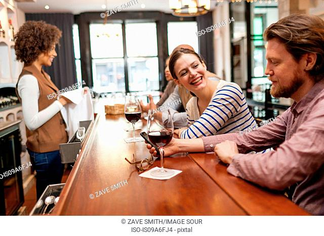 Woman and man at bar chatting and checking cell phone