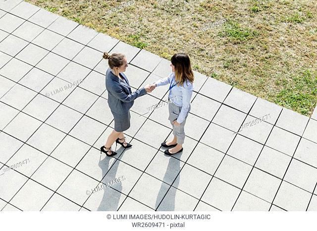 Two businesswomen shaking hands outdoors