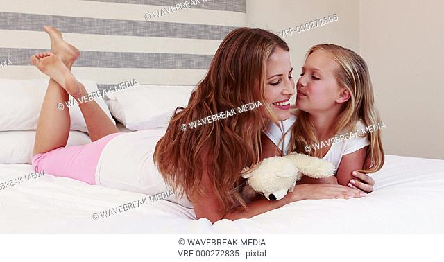 Mother and daughter talking on bed