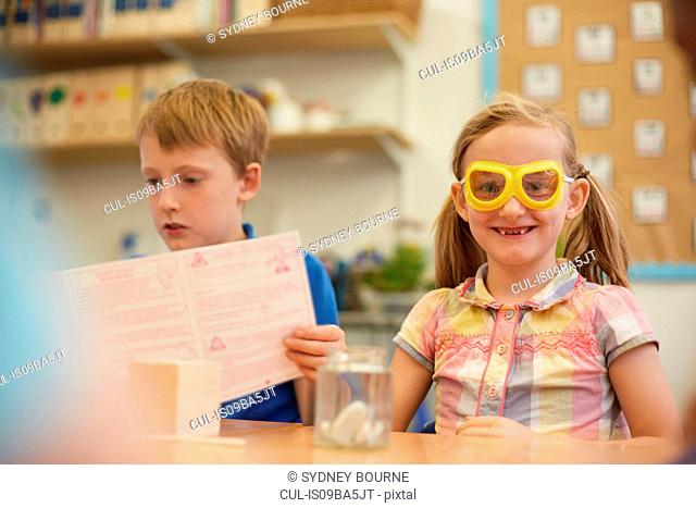 Primary schoolboy and girl doing experiment in classroom