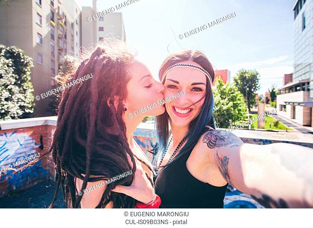 Young woman kissing friend on cheek
