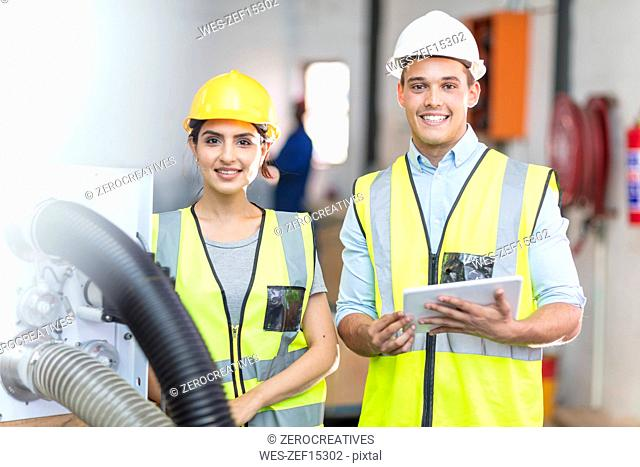 Portrait of two smiling technicians with tablet