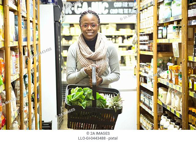 Portrait of woman holding basket full of groceries in health shop in health store, Johannesburg, South Africa
