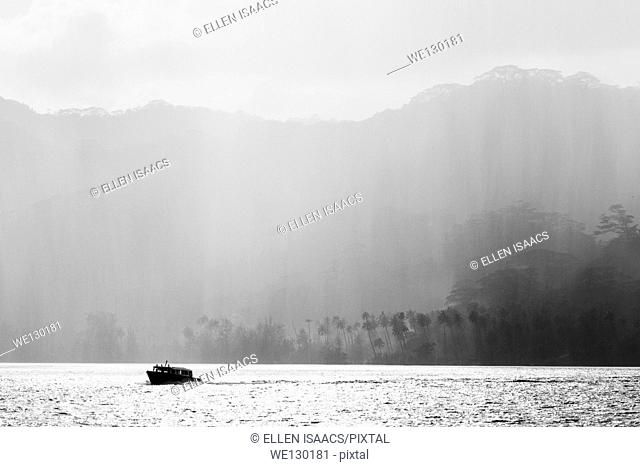 Silhouette of boat against rain shower falling on layers of tropical trees in French Polynesia