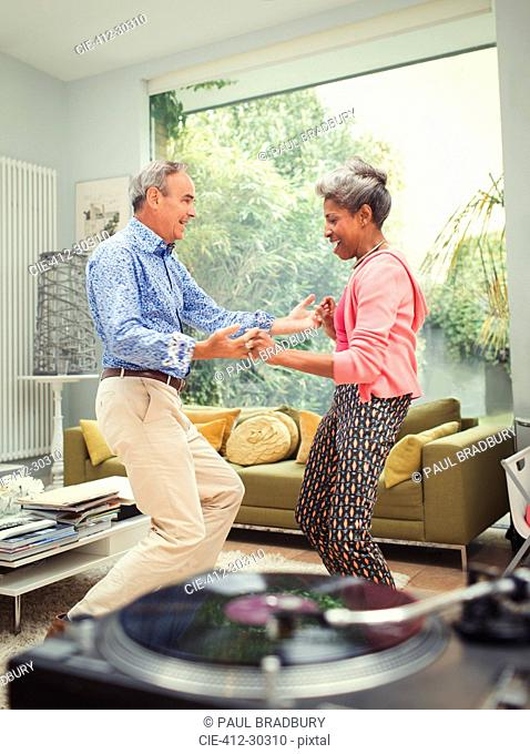 Playful mature couple dancing behind record player in living room