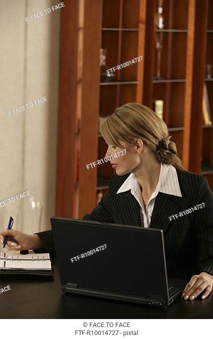 A blonde businesswoman looking over her appointment diary with a laptop beside her