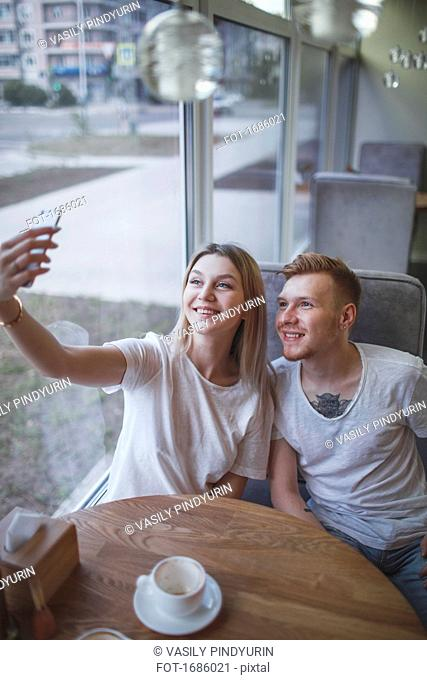 High angle view of young couple taking selfie with mobile phone while sitting at restaurant