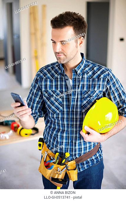 Construction worker using mobile phone during the working. Pilzno, Poland