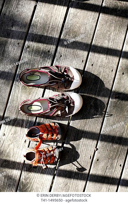 A pair of adult, and a pair of child's, water shoes, laying out on a porch in the summer sun to dry
