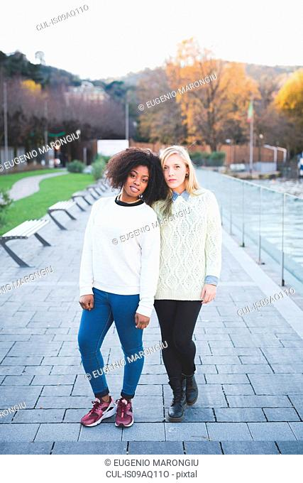 Portrait of two young female friends in lakeside park, Como, Italy