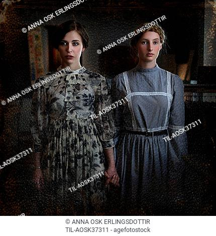 Two females wearing period dresses standing beside each other