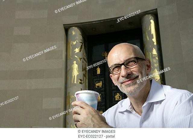 mature man portrait, looking at camera, drinking coffee