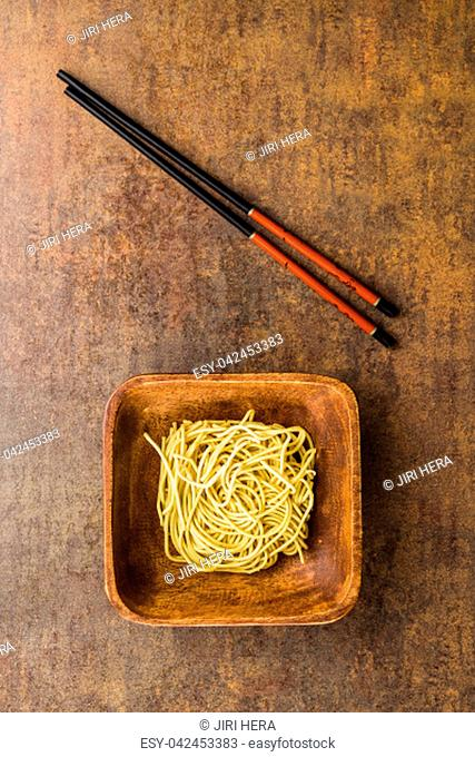 Uncooked instant chinese noodles and chopsticks. Top view