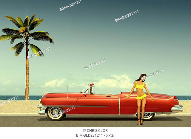 Caucasian woman leaning on old-fashioned convertible car at ocean