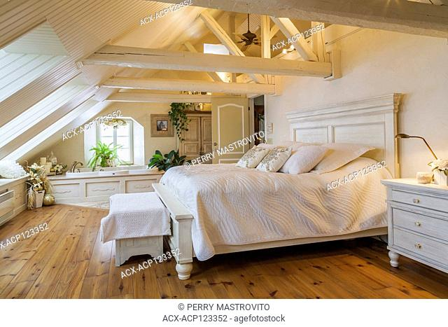 King size antique wooden bed in master bedroom in the attic of an old (circa 1840) Canadiana cottage style home, Quebec, Canada