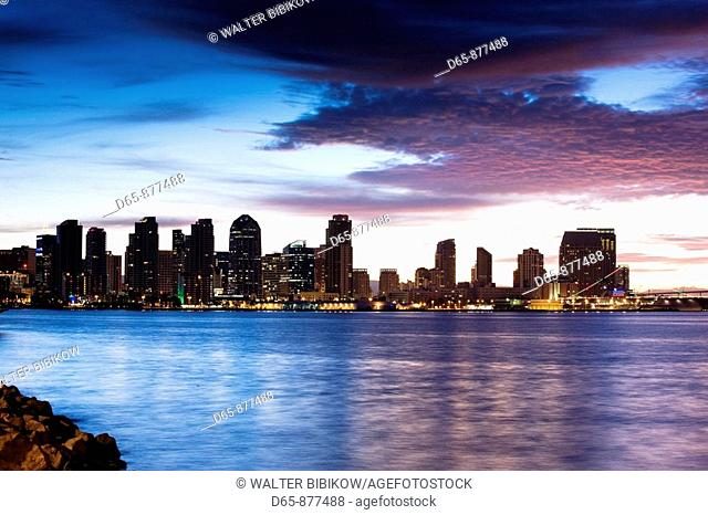 Waterfront city view with USS Midway aircraft carrier from Harbor Island at dawn, San Diego, California, USA