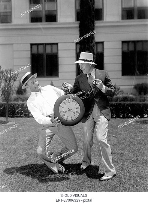 Two men wrestling with an oversized pocket watch All persons depicted are not longer living and no estate exists Supplier warranties that there will be no model...