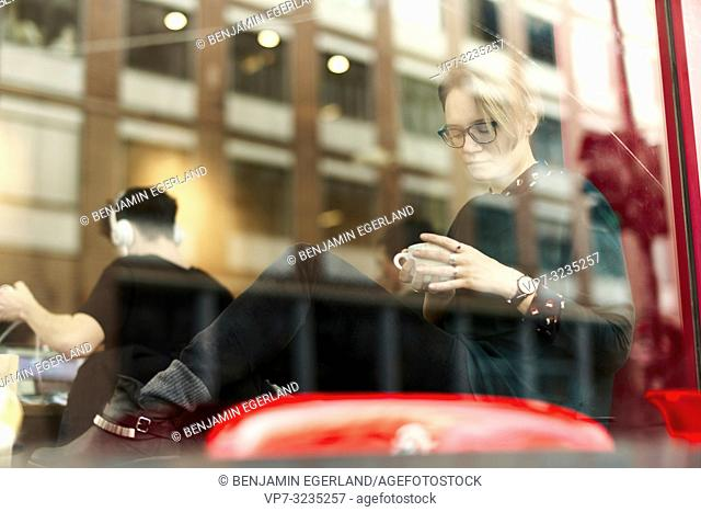 woman behind glass window indoors in coffee shop, in Munich, Germany