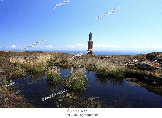 First duke of Sutherland monument on Ben Bhraggie with small lochan in the foreground and the North sea in the background