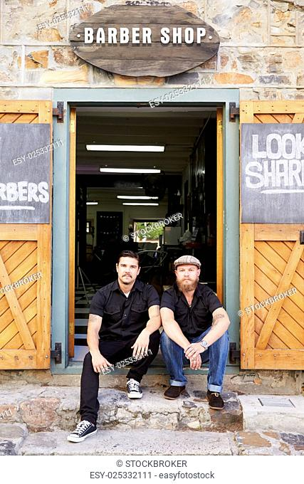 Portrait Of Two Hipster Barbers Standing Outside Shop