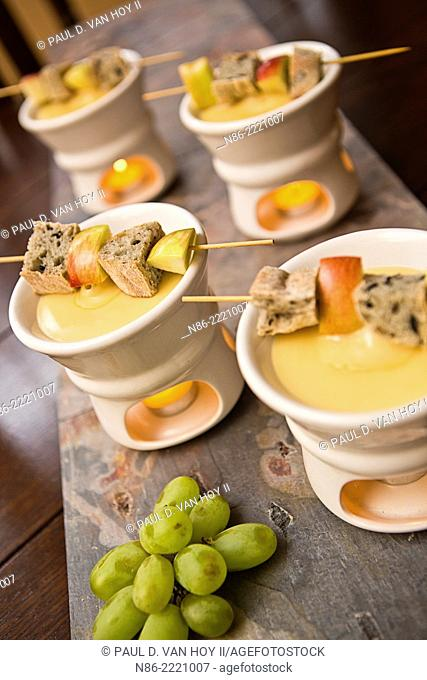 parmesan fondue with bread cubes and apple slices