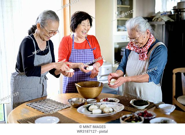 Three older women standing round a table in a kitchen, making sushi