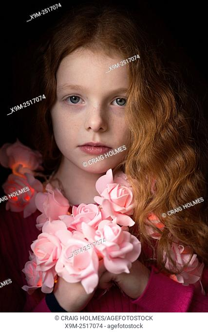 Portrait of a little girl with a rose garland around her neck