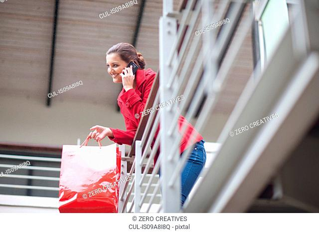 Young woman on cellphone in shopping mall