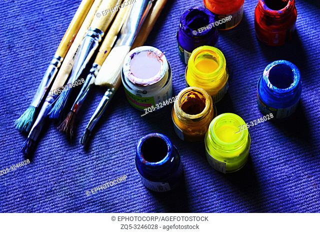 Poster colors and brushes for painting on a blue background