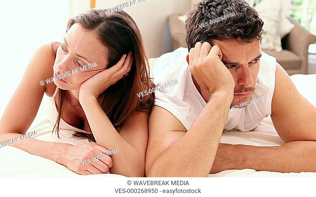 Unhappy couple lying on bed not talking