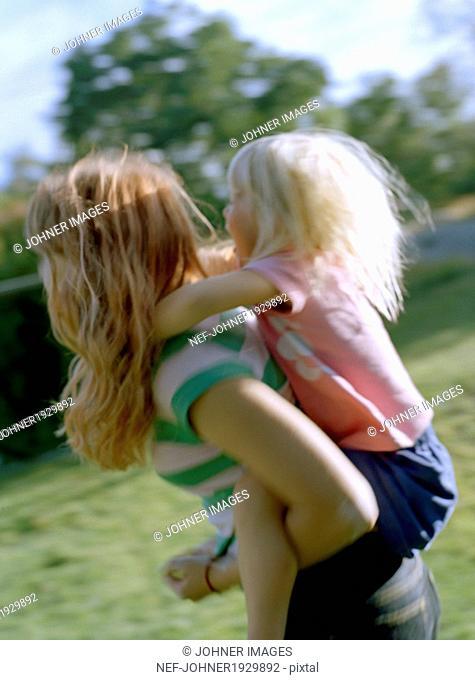 Girl giving sister piggyback ride