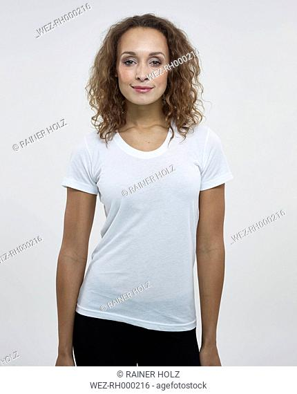 Portrait of young woman against white background, smiling